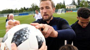L'attaquant anglais Harry Kane signe un ballon tendu par un supporter, à Zelenogorsk (Russie), le 13 juin 2018. (PAUL ELLIS / AFP)