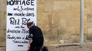 Un homme s'agenouille devant le panneau annonçant la marche en hommage aux victimes de l'accident de car de Puisseguin, le 23 octobre 2015 à Petit-Palais (Gironde). (JEAN-PIERRE MULLER / AFP)