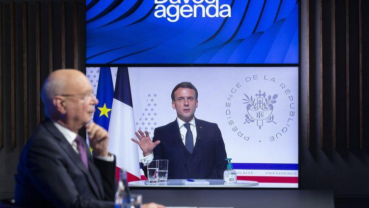 Visioconférence du Forum de Davos. Klaus Schwab, fondateur de ce Forum (à gauche) et Emmanuel Macron, président de la République, sur l'écran (à droite), le 26 janvier 2021. (SALVATORE DI NOLFI / KEYSTONE)