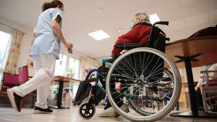 Une personne âgée en fauteuil roulant en Ehpad, aux côtés des soignants, dans le Finistère (Bretagne), le 25 novembre 2020. (LIONEL LE SAUX / MAXPPP)