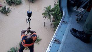 Un homme est hissé à bord d'un hélicoptère des forces aériennes indiennes lors d'une opération d'évacuation dans l'Etat du Kerala en Inde, le 18 août 2018. (HANDOUT / INDIAN DEFENCE MINISTRY / AFP)