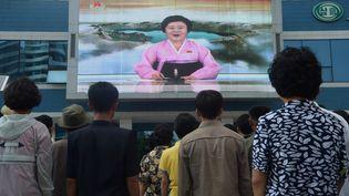Des habitants de Pyongyang (Corée du Nord) regardent la présentatrice Ri-Chun hee annoncer le sixième essai nucléaire du pays à la télévision, le dimanche 3 septembre 2017. (KIM WON-JIN / AFP)