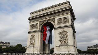L'Arc de Triomphe décoré d'un drapeau français, le 14 juillet 2019 à Paris. (LUDOVIC MARIN / AFP)