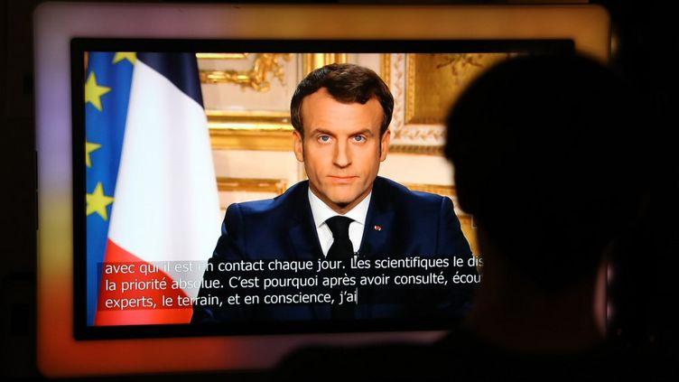 Un homme regarde le président de la République Emmanuel Macron annoncer le confinement de la population pour lutter contre la propagation du Covid-19, le 16 mars 2020 à Paris. (LUDOVIC MARIN / AFP)