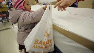Campagne et collecte 2011 de la banque alimentaire à Marseille. Un enfant donne un paquet devantun supermarché, le 28 novembre 2011. (SEGURAN / ZEPPELINNETWORK / SIPA)
