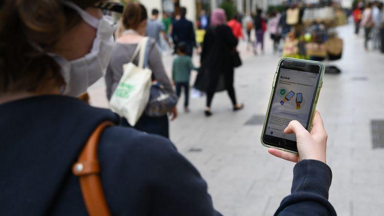 De nombreuses critiques pointent du doigt le coût engendré par StopCovid, utilisée ici dans la rue par une citoyenne à Angers. (JOSSELIN CLAIR / MAXPPP)