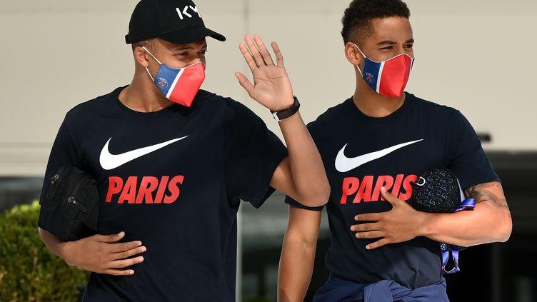 Les joueurs du PSG Kylian Mbappé et Thilo Kehrer quittent leur hôtel pour participer à l'entraînement, le 17 août 2020, avant le match contre Leipzig le lendemain à Lisbonne. (FRANCK FIFE / AFP)
