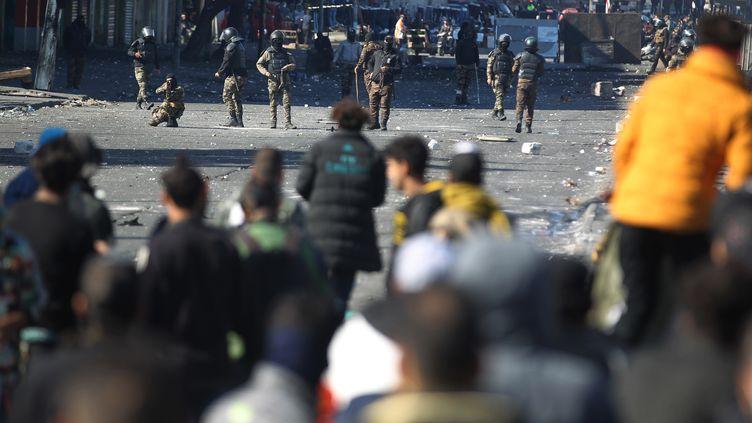 Des manifestants face aux forces de l'ordre sur une place de Bagdad, en Irak, le 27 janvier 2020 (AHMAD AL-RUBAYE / AFP)