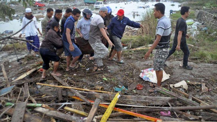 Des habitants transportent des corps après le tsunami qui a déferlé sur Palu, en Indonésie. (AP / SIPA)
