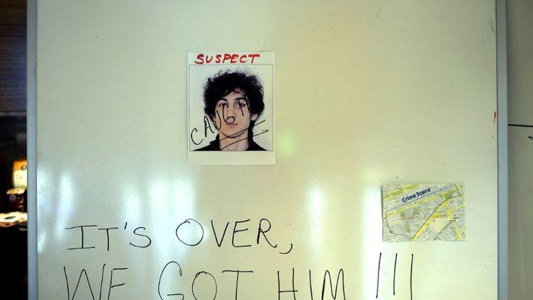 """""""C'est fini, nous l'avons eu !"""" Cette inscription est écrite sur un panneau où est affichée la photo de Djokhar Tsarnaev après son arrestation, samedi 20 avril 2013, à Boston (Etats-Unis). (TIMOTHY A. CLARY / AFP)"""