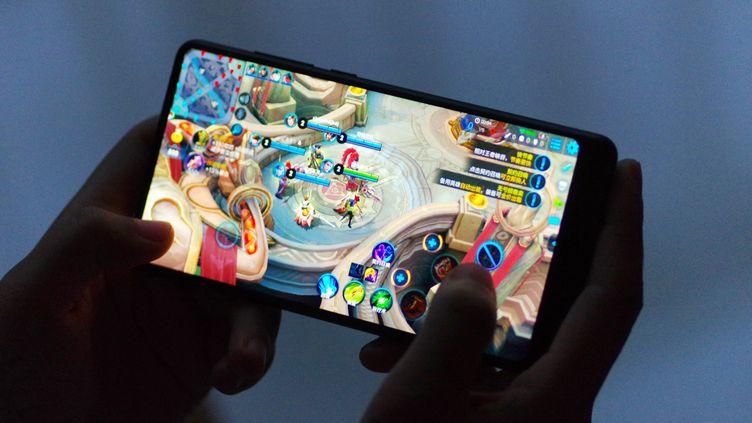 """Image d'illustration. Une personne joue sur son mobile à """"King of Glory"""" (2018). (DA QING / IMAGINECHINA)"""