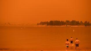 Des habitants de Nouvelle-Galles du Sud sous un nuage orangéà cause dela fumée des feux de forêts qui ravagent le pays depuis quatre mois. (SAEED KHAN / AFP)