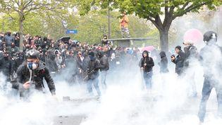 Des manifestants affrontent les forces de l'ordre, dans la fumée des grenades lacrymogènes, à Paris, le 9 avril 2016. (JOEL SAGET / AFP)