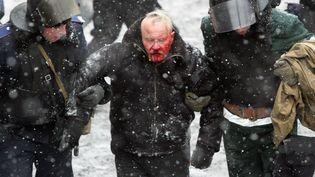 La police anti-émeute ukrainienne embarque un manifestant blessé, mercredi 22 janvier 2014 à Kiev (Ukraine). (ANATOLII BOIKO / AFP)