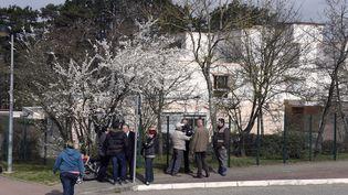 Des parents et des enquêteurs devantl'école de Mas de la Ras, à Villefontaine (Isère), le 24 mars 2015. (PHILIPPE DESMAZES / AFP)