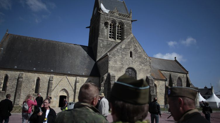 Des passants devant l'église de Sainte-Mère-Eglise (Manche), le 31 mai 2014. (CHARLY TRIBALLEAU / AFP)