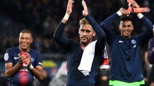 Les joueurs du PSG Kylian Mbappé, Neymar et Alphonse Areola applaudissent en direction des tribunes du Parc des Princes, après leur victoire face à Lyon en Ligue 1,le 7 octobre 2018. (FRANCK FIFE / AFP)
