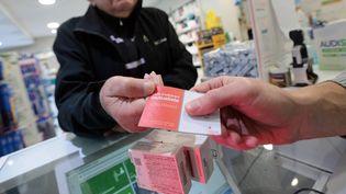 Un client d'une pharmacie présente sa carte de mutuelle pour l'achat de médicaments. Photo d'illustration. (FRANCOIS DESTOC / MAXPPP)