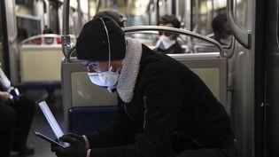 Un jeune homme masqué regarde son smartphone. (ALAIN JOCARD / AFP)