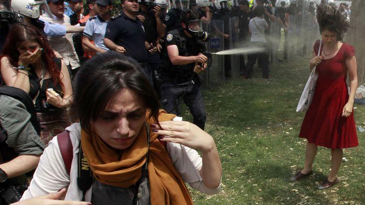 Un policier turc asperge une manifestante de gaz lacrymogène sur la place Taksim à Istanbul (Turquie), le 28 mai 2013. (OSMAN ORSAL / REUTERS)