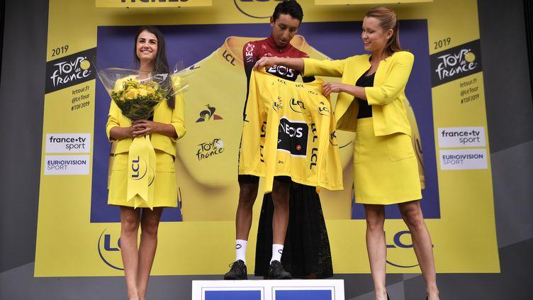 """Egan Bernal (INEOS) entouré par deux """"miss"""", sur un podium du Tour de France 2019. (MARCO BERTORELLO / AFP)"""