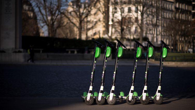 Des trottinettes électriques stationnées sur un trottoir, près de la tour Eiffel à Paris, le 13 décembre 2018. (LIONEL BONAVENTURE / AFP)