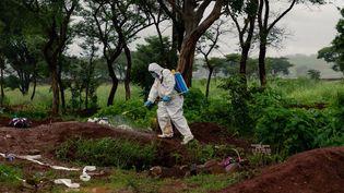 Un employé pulvériseun désinfectant autour de la tombe d'une personne décédée du Covid-19, au cimetière Glen Forest, à Harare, le 14 janvier 2021. (JEKESAI NJIKIZANA / AFP)