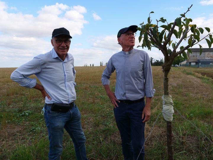 De gauche à droite : Thierry Loyer, membre de l'association, le père Jean-Marie Lioult, initiateur du projet... et le tout premier arbre planté, un prunier ! (ISABELLE MORAND / RADIO FRANCE / FRANCE INFO)