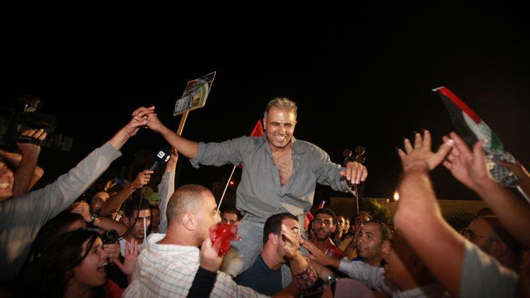 La foule acclame un ancien détenu palestinien, libéré dans le cadre des négociations de paix avec Israël, mercredi 14 août 2013 à Ramallah (Cisjordanie). (ABBAS MOMANI / AFP)