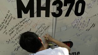 Un homme écrit un message sur un panneau en mémoire des disparus du vol MH370, le 8 mars 2015, à Kuala Lumpur (Malaysie). (AHMAD YUSNI / NURPHOTO / AFP)