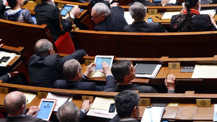Des députés devant leurs tablettes alors qu'ils siègent à l'Assemblée nationale, à Paris, le 19 février 2013. (MIGUEL MEDINA / AFP)
