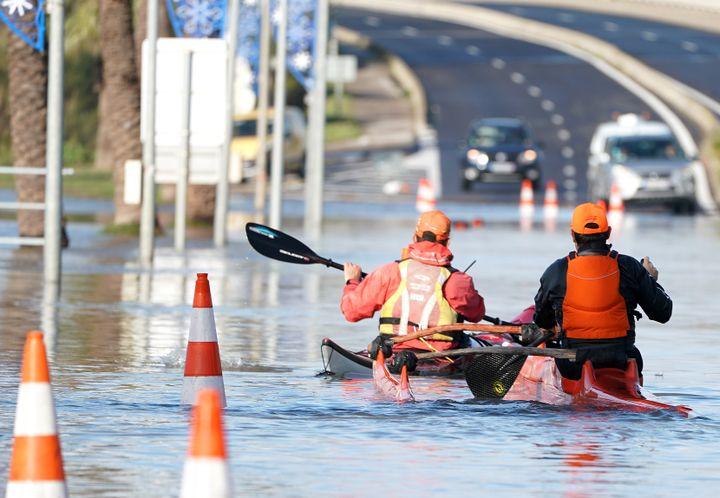 Deux hommes font du kayak sur une route inondée à Palavas-les-Flots (Hérault), le 23 novembre 2019. (PASCAL GUYOT / AFP)