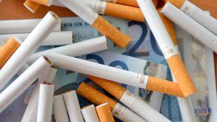 Des cigarettes et des billets de banque, sur une table à Lille (Nord), le 17 juillet 2013. (DENIS CHARLET / AFP)