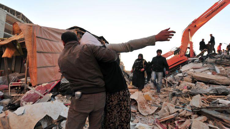 Des rescapés du tremblement de terre devant les ruines de leur maison, à Ercis, dans l'est de la Turquie, lundi 24 octobre 2011. (MUSTAFA OZER / AFP)