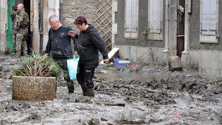 Des habitants de Saint-Béat (Haute-Garonne) qui regagnaient leurs maisons découvrent l'étendue des dégâts causés par les inondations, le 19 juin 2013. (PASCAL PAVANI / AFP)