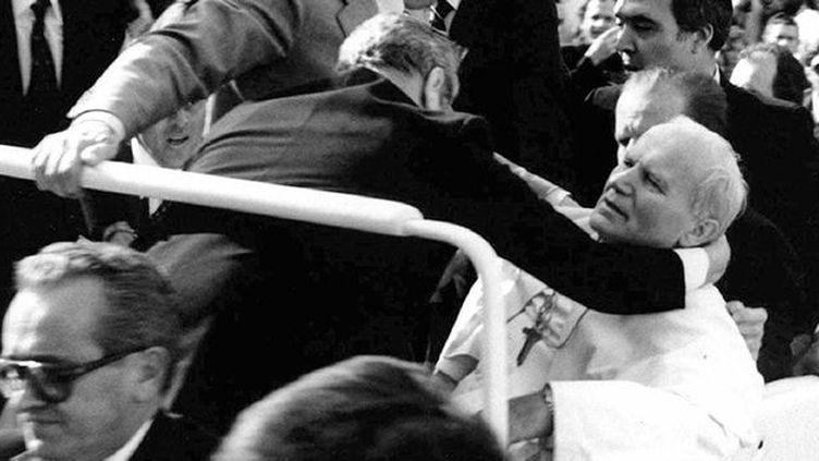 Le pape Jean-Paul II, grièvement blessé par balles, soutenu par ses gardes du corps, le 13 juin 1981. (Reuters)