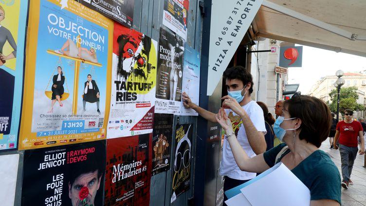 Les affiches pour le Off sont collées par deux personnes masquées, le 4 juillet 2021. (REY J?R?ME / MAXPPP)