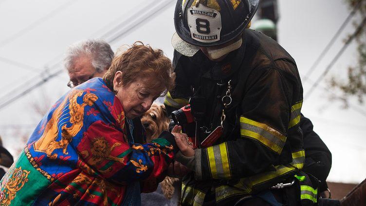 Un pompier aide une femme à monter à bord d'un camion et à quitter une zone sinistrée deLittle Ferry dans le New Jersey, après le cyclone Sandy (Etats-Unis), le 30 octobre 2012. (ANDREW BURTON / GETTY IMAGES NORTH AMERICA / AFP)