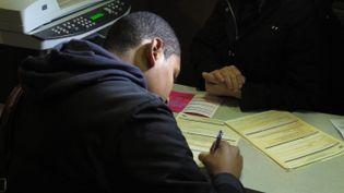 Amine, 18 ans, remplit le formulaire d'inscription. (THOMAS BAÏETTO / FTVi)