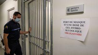 Un gardien de prison portant un masque de protection ouvre la porte d'un couloir menant au parloir de la prison de la Santé, à Paris, en novembre 2020. (BERTRAND GUAY / AFP)
