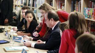 """François Hollande choisit avec les enfants les photos pour le prochain numéro du journal """"Mon Quotidien"""", à Paris, le 22 janvier 2015. (REMY DE LA MAUVINIERE / AFP)"""
