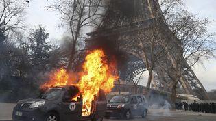 Une voiture de l'opération Sentinelle incendiée devant la Tour Eiffel à Paris, le 9 février 2019. (ZAKARIA ABDELKAFI / AFP)