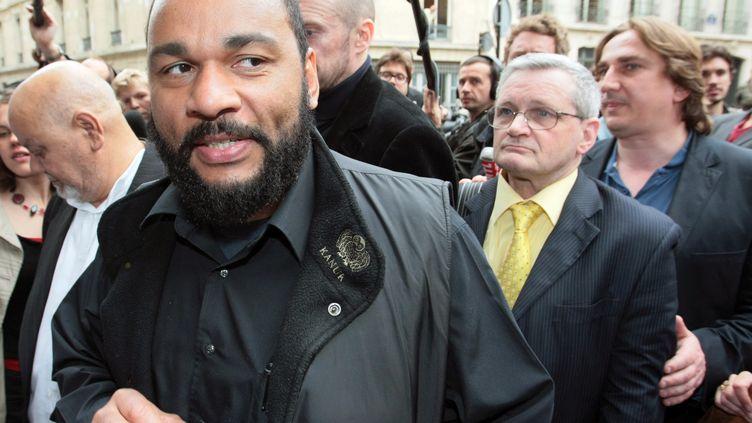Le polémiste Dieudonné, le 13 mai 2009 au ministère de l'Intérieur, à Paris. Pierre Panet, candidat sur une liste FN parisienne, se trouve derrière lui, avec une chemise jaune. (JACQUES DEMARTHON / AFP)