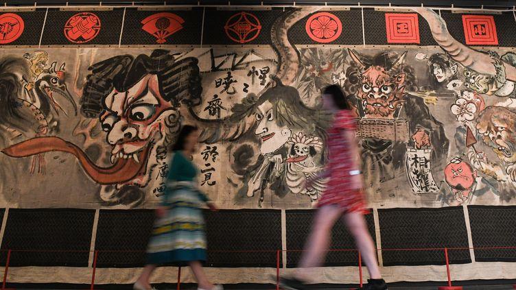 Des employées du British Museum passent devant un rideau historique de théâtre Manga peint par l'artiste japonaisKawanabe Kyosaipour le théâtre Shintomi, à Londres, le 22 mai 2019. (DANIEL LEAL-OLIVAS / AFP)