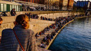 """Cette image prise le 6 mars 2021 à Lyon, illustre le non-respect des gestes barrières le long des quais de Saône, à l'heure du couvre-feu. Le retour à la vie """"normale"""" peut effrayer tous ceux qui craignent rassemblements et contamination. (ROBERT DEYRAIL / GAMMA-RAPHO / GETTY IMAGES)"""