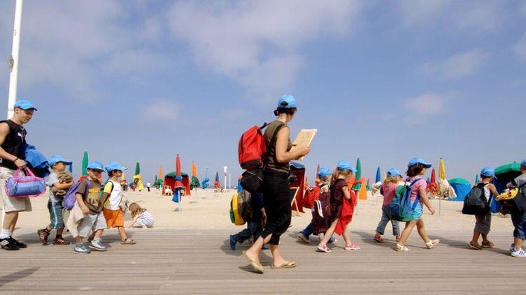 Des enfants en colonie de vacances marchent sur les planches de la plage de Deauville, le 10 août 2005, encadrés par des moniteurs. (MYCHELE DANIAU / AFP)