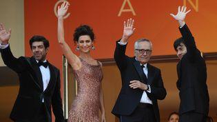 L'équipe du film Le Traître salue le public avant d'entrer dans le Palais des festivals pour la projection du film. (LOIC VENANCE / AFP)