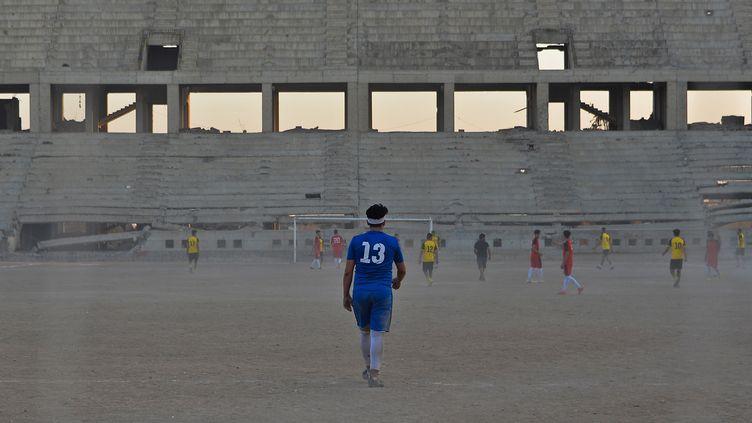 Les joueurs du FC Al-Mossoul s'entraînent dans le stade Al-Idara al-Mahalia, qui a été ravagé et qui servait autrefois de dépôt d'armes aux combattants du groupe d'État islamique, près de la ville de Mossoul, dans le nord de l'Irak, le 22 octobre 2020.  (ZAID AL-OBEIDI / AFP)