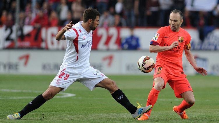 Koke au duel avec Andrés Iniesta lors de Séville-Barça (saison 2014-2015). (CRISTINA QUICLER / AFP)