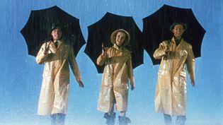"""Debbie Reynolds (au centre), entourée de Gene Kelly et Donald O'Connor, dans """"Chantons sous la pluie"""", en 1952. (KOBAL / AFP)"""